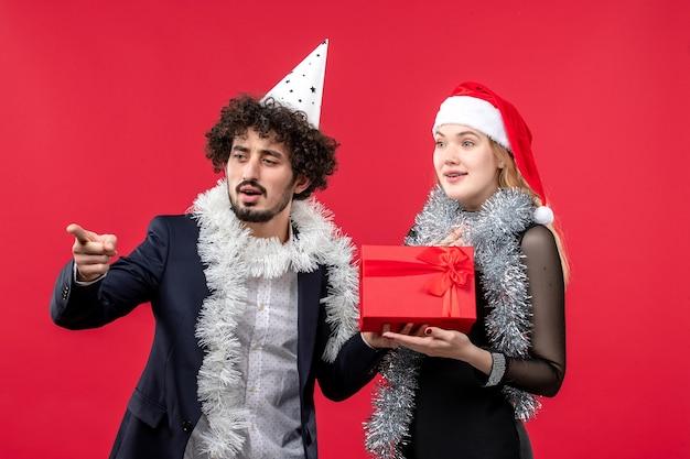Junges paar der vorderansicht mit geschenk, das auf roter schreibtischparty-weihnachtsliebe feiert