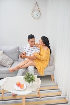 Junges paar entspannt sich im luxuriösen zuhause mit tablet-computern, die im wohnzimmer auf der sofacouch lesen.