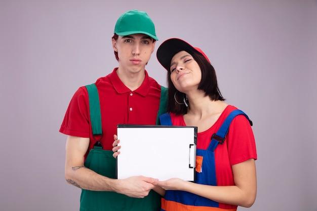 Junges paar ernster kerl und erfreutes mädchen in bauarbeiteruniform und mütze, das klemmbrettmädchen mit geschlossenen augen hält und zeigt