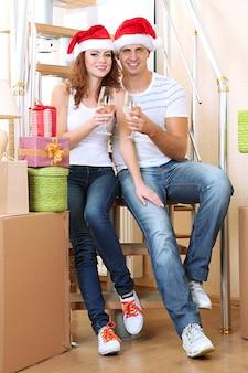 Junges paar feiert silvester im neuen zuhause auf treppenhintergrund