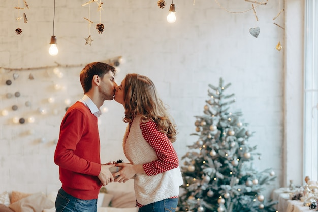 Junges paar geben sich gegenseitig weihnachtsgeschenke