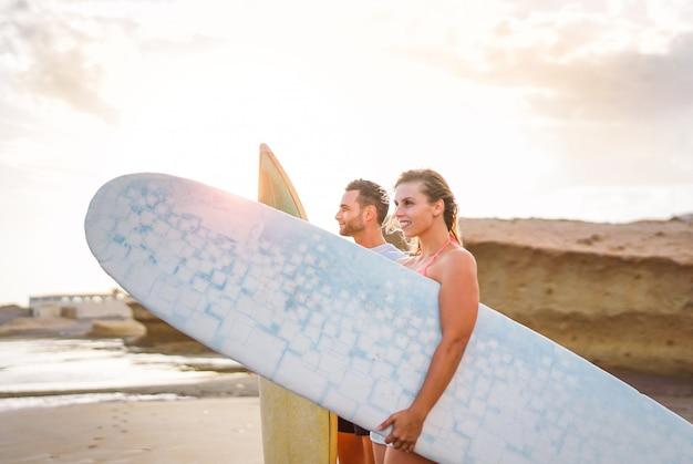 Junges paar glücklicher surfer, die am strand stehen und surfbretter halten, die vorbereiten, auf hohen wellen während eines herrlichen sonnenuntergangs zu surfen - menschen, lebensstil, extremsportkonzept - fokus auf mann