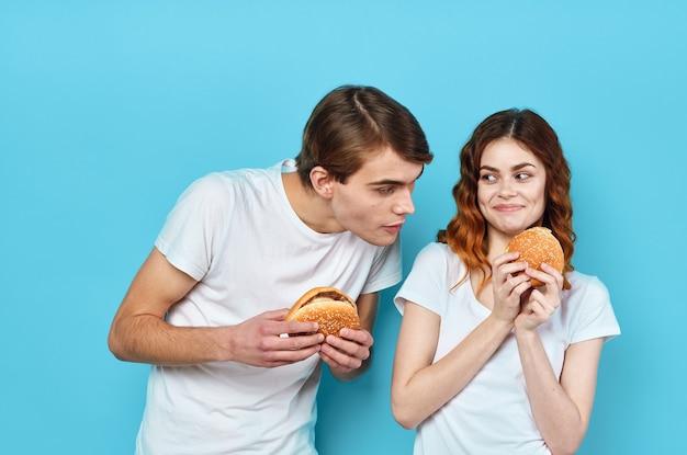 Junges paar hamburger in den händen snack lifestyle blauen hintergrund