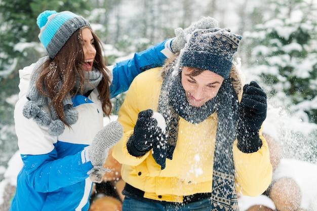 Junges paar hat spaß während der schneeballschlacht