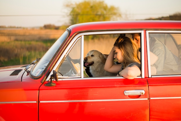 Junges paar im auto mit ihrem hund