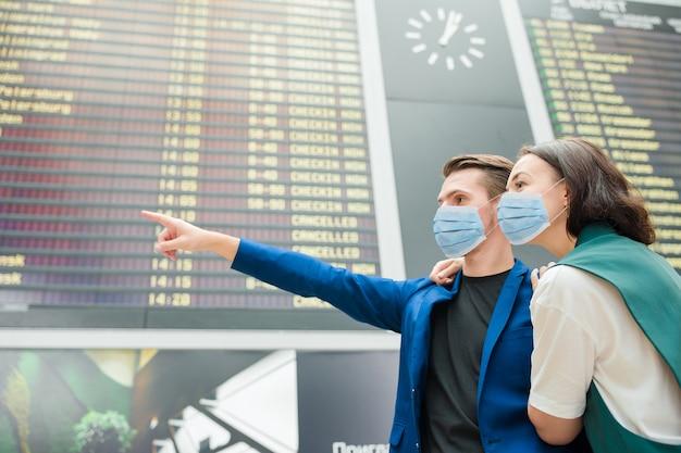 Junges paar im internationalen flughafen, das die fluginformationstafel betrachtet