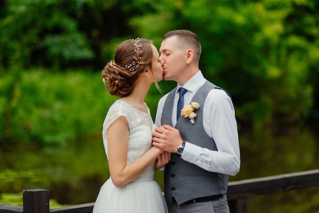 Junges paar im liebesküssen, -bräutigam und -braut im hochzeitskleid