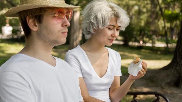 Junges paar im park, das burger zusammen isst