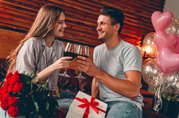 Junges paar im schlafzimmer mit gläsern wein, geschenk und roten rosen. valentinstag. jubiläum. geburtstag.