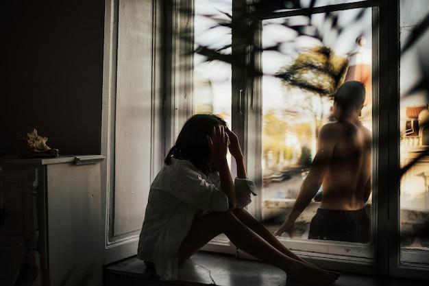 Junges paar im streit und wütend. mann stehend am balkon und frau, die auf fensterbank sitzen.