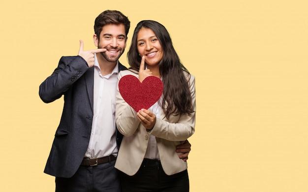 Junges paar im valentinstag lächelt und zeigt in den mund