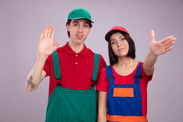 Junges paar in bauarbeiteruniform und mütze aufgeregter kerl erfreute mädchen, das leeres handmädchen zeigt, das die hand zur kamera ausstreckt