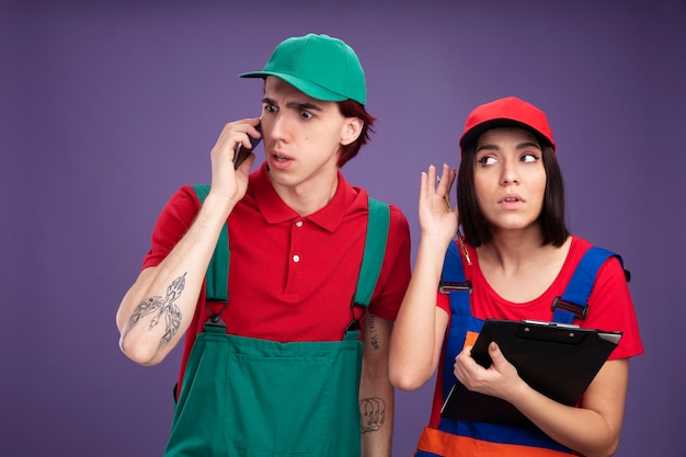 Junges paar in bauarbeiteruniform und mütze besorgter kerl, der am telefon spricht und neugieriges mädchen hält, das bleistift und zwischenablage hält, die seite betrachten, die telefongespräch isoliert hört