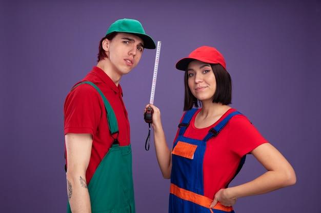 Junges paar in bauarbeiteruniform und mütze, das in der profilansicht steht, verwirrter kerl erfreutes mädchen, das die hand an der taille hält und das bandmessgerät hält