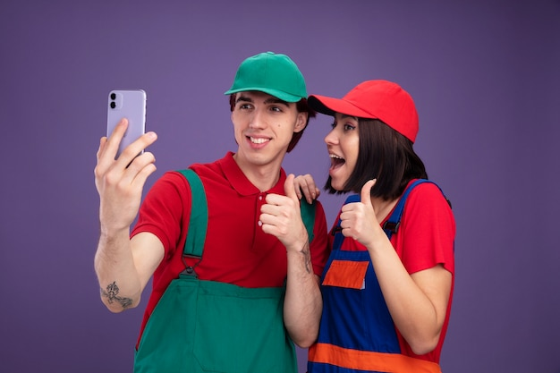 Junges paar in bauarbeiteruniform und mütze, das selfie zusammen nimmt lächelnder kerl aufgeregtes mädchen, das daumen hoch mädchen zeigt, das hand auf der schulter des kerls lokalisiert auf purpurroter wand hält
