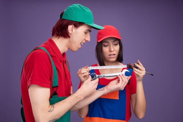 Junges paar in bauarbeiteruniform und mütze konzentriertes mädchen, das ein bandmeter hält und anschaut, aufgeregter kerl, der in der profilansicht steht und einen schraubenschlüssel hält und betrachtet
