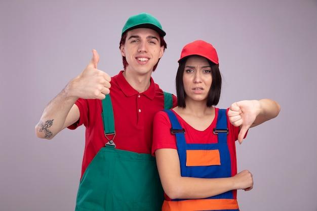 Junges paar in bauarbeiteruniform und mütze lächelnder kerl, der daumen nach oben zeigt, unzufriedenes mädchen, das beide daumen nach unten zeigt