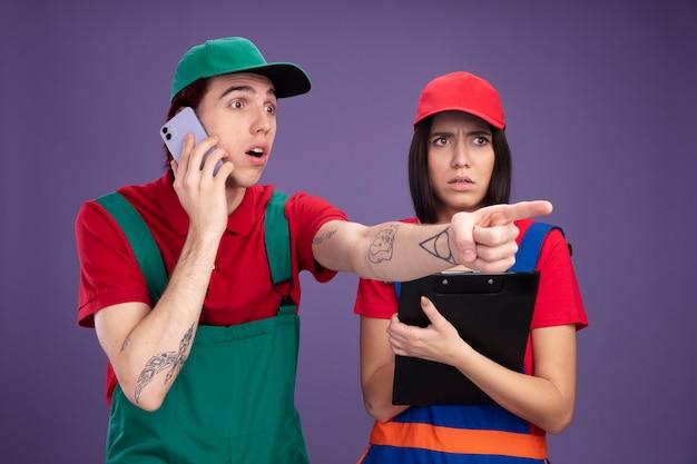 Junges paar in bauarbeiteruniform und mütze mit blick auf die seite überraschter kerl, der am telefon spricht und auf die seite zeigt verwirrtes mädchen mit zwischenablage