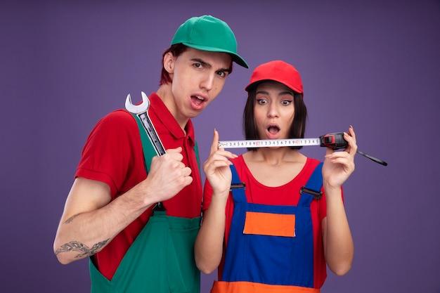 Junges paar in bauarbeiteruniform und mütze überraschte mädchen, das bandmeter selbstbewusster kerl mit schraubenschlüssel hält und betrachtet
