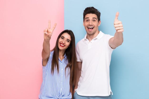 Junges paar in der freizeitkleidung lächelnd und friedenszeichen zeigend, lokalisiert über bunte wand