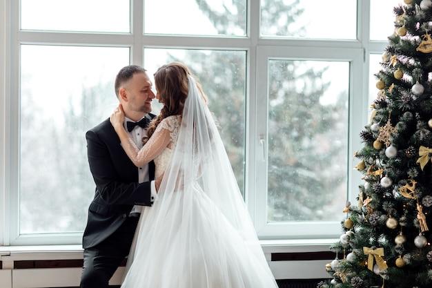 Junges paar in der liebe braut und bräutigam, die im studio auf hintergrund mit weihnachtsbaum in ihrem hochzeitstag an weihnachten nahe dem großen panoramafenster verziert aufwirft.