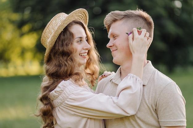 Junges paar in der liebe im freien. atemberaubendes sinnliches porträt im freien des jungen stilvollen modepaares, das im sommer im feld aufwirft