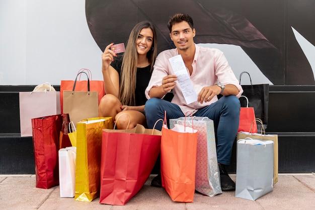 Junges paar in der nähe von bunten einkaufstüten