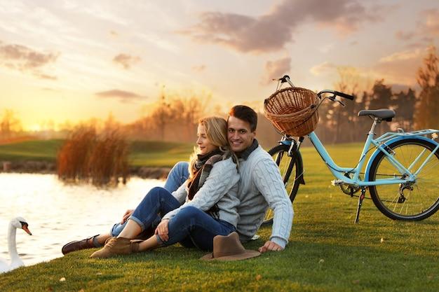 Junges paar in der nähe von see mit schwan bei sonnenuntergang. perfekter ort für ein picknick