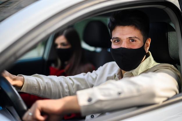 Junges paar in einem auto, das schutzmasken gegen covid 19 coronavirus-pandemie trägt