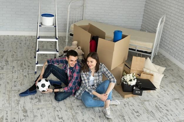 Junges paar in einem neuen zuhause, das sich auf dem hintergrund großer kisten entspannt. konzept housewarming, begann zusammen zu leben.
