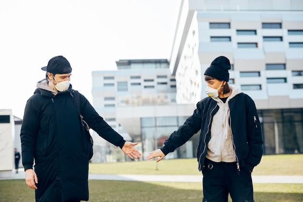 Junges paar in freizeitkleidung, das versucht, sich gegenseitig mit distanz auf der straße zu berühren, während coronavirus, soziale distanz, während covid19