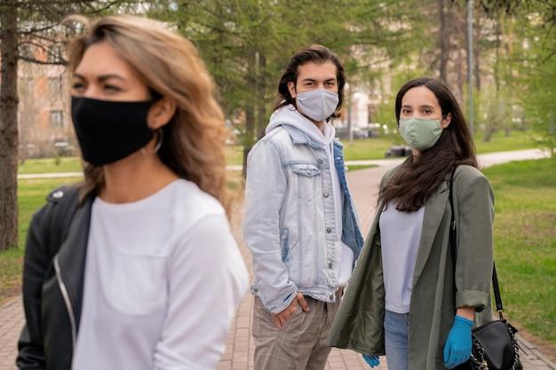 Junges paar in gesichtsmasken, die mit furcht an frau suchen, die straße während der coronavirus-pandemie überquert