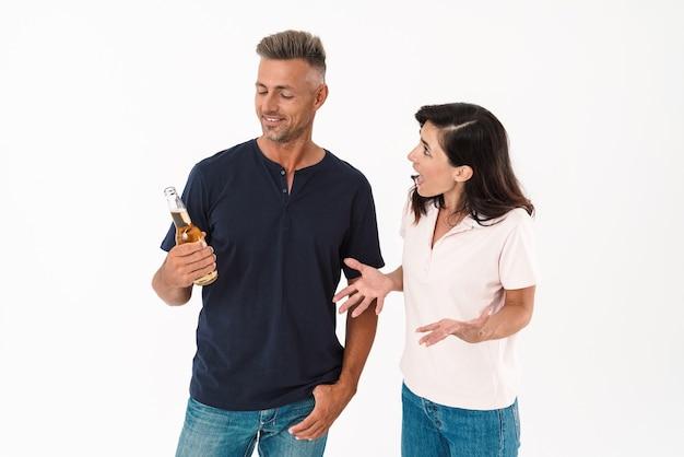 Junges paar in lässigem outfit steht isoliert über weißer wand, frau schreit ihren freund an, während er bier trinkt