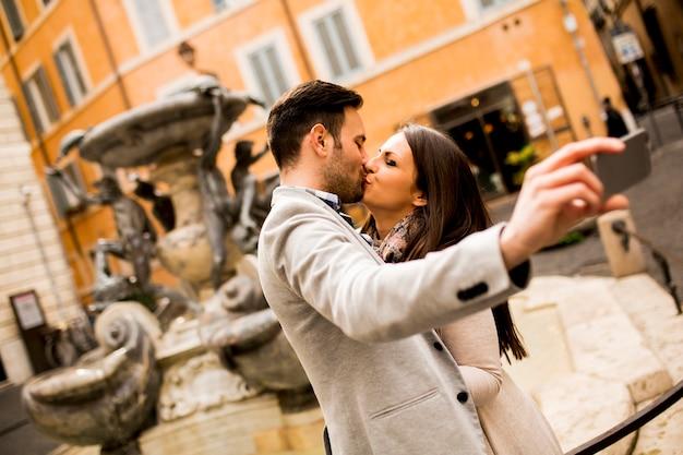 Junges paar in liebe küssen und nimmt selfi in rom