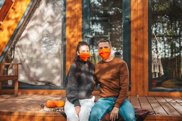 Junges paar in masken, die auf der terrasse ihres hauses im herbst sitzen
