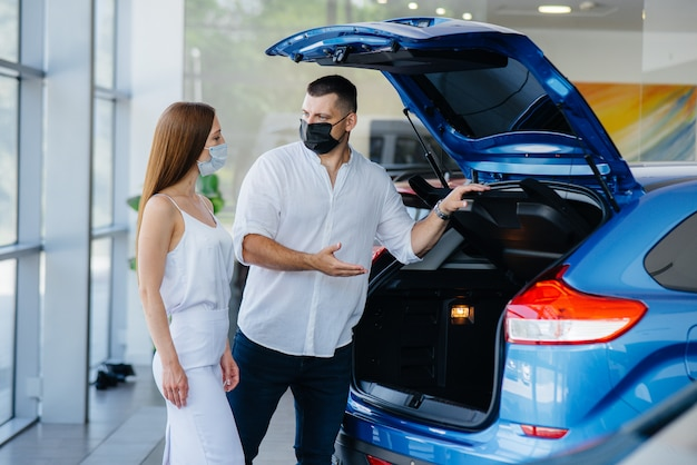 Junges paar in masken wählt ein neues fahrzeug aus und konsultiert einen vertreter des autohauses in der zeit der pandemie. autoverkauf und leben während der pandemie.