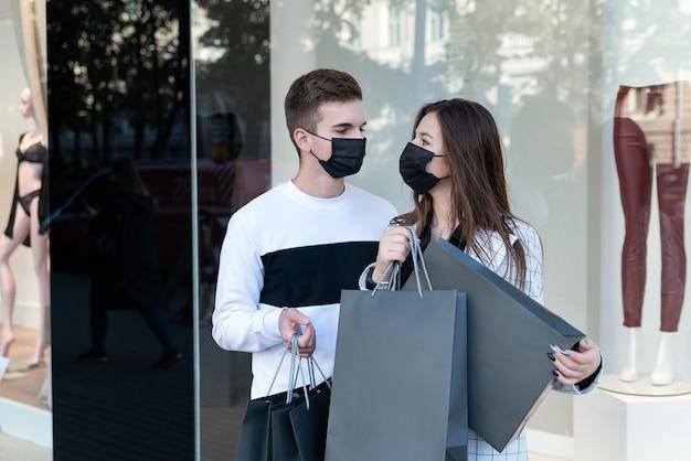 Junges paar in medizinischen masken nach dem einkaufen im einkaufszentrum mit paketen in den händen. black friday konzept.
