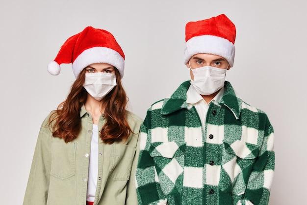 Junges paar in medizinischen masken weihnachten, das spaß hat