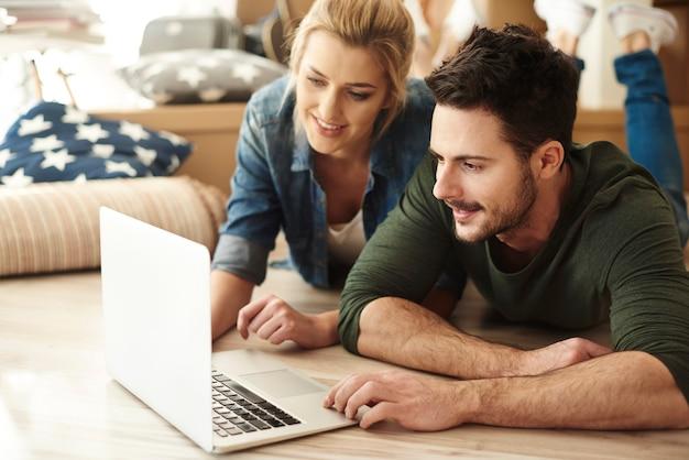 Junges paar in neuer wohnung mit laptop