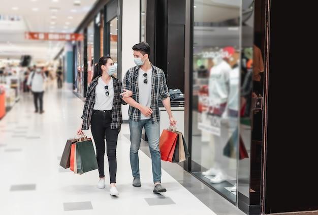 Junges paar in schutzmaske, das mehrere papiereinkaufstaschen hält, die im korridor des großen einkaufszentrums spazieren gehen?