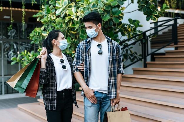 Junges paar in schutzmaske mit mehreren papiereinkaufstüten