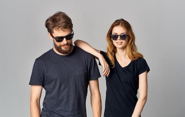 Junges paar in schwarzen t-shirts sonnenbrille studio romantik kommunikation eleganten stil
