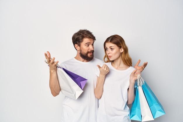 Junges paar in t-shirts beim einkaufen von rabattverkaufsspaß