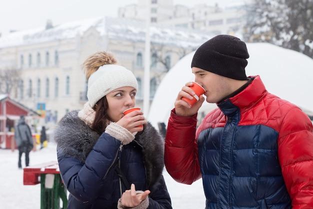 Junges paar in warmer winterkleidung, schals und strickmützen, die auf einem winterlichen stadtplatz heiße getränke trinken