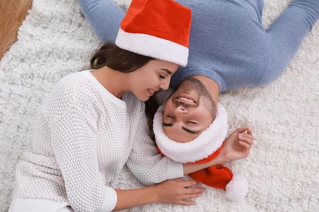 Junges paar in weihnachtsmützen auf pelzteppich drinnen liegend
