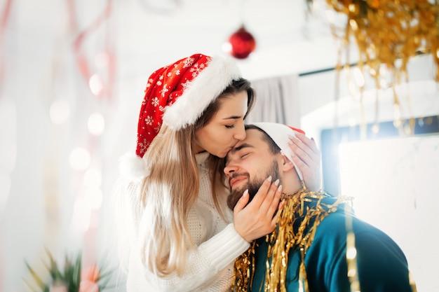 Junges paar in weihnachtsmützen schmückt das haus für weihnachten und neujahr