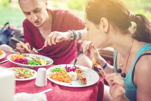 Junges paar isst gemüse und fisch im freien