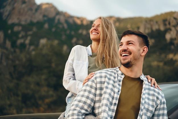 Junges paar ist auf romantischer fahrt in die berge mit dem auto