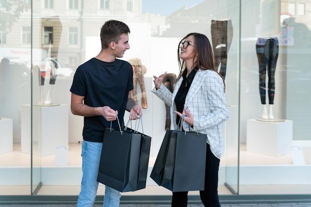Junges paar käufer mit taschen im schaufenster. schwarzer freitag, verkauf