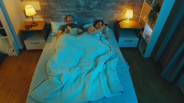 Junges paar kann wegen vollmond nicht schlafen. junger mann, der ein buch liest. freundin mit smartphone.